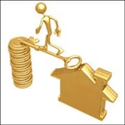 Man walking across a gold key bridging a house and a stack of gold coins