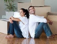 Couple sitting on floor amongst moving boxes