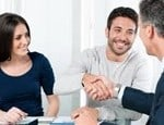 Young couple shaking mortgage brokers hand