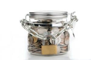 money saved locked in a large jar with a chain and padlock