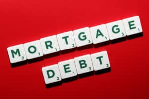 mortgage debt spelled out on scrabble tokens